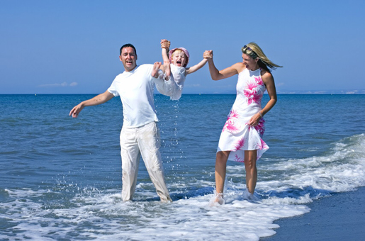 Family enjoying a day at the beach © iStock