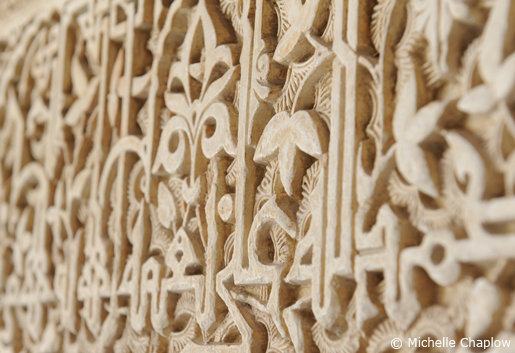 Plant motifs and decorative inscriptions of calligraphy running horizontally across walls in the Alhambra, Granada